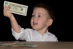 Lycklig pojke med dollar i händer Royaltyfri Bild