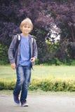 Lycklig pojke med en ryggsäck som går skola Utbildning tillbaka till skolan, folkbegrepp Royaltyfri Bild