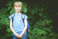 Lycklig pojke med en ryggsäck som går till skolan Utbildning tillbaka till skolan, folkbegrepp Royaltyfri Bild
