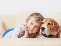 Lycklig pojke med hans hund som ligger på soffan Royaltyfri Bild