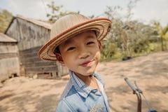 Lycklig pojke med hatten på den lantliga gatan i Vietnam Royaltyfri Foto