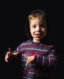 Lycklig pojke med hoodien som står över svart bakgrund Fotografering för Bildbyråer