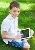Lycklig pojke med minnestavlan Royaltyfri Foto