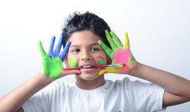 Lycklig pojke med målarfärg som har gyckel Royaltyfri Bild