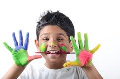 Lycklig pojke med målarfärg som har gyckel Arkivfoto