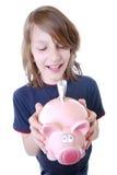 Lycklig pojke med piggybank Royaltyfria Foton