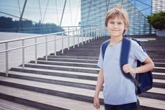 Lycklig pojke med skolapåsen i staden Utbildning tillbaka till skolan, lopp, fritidbegrepp Royaltyfri Fotografi