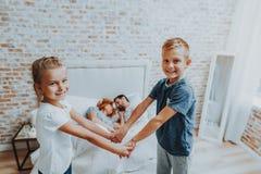 Lycklig pojke och flicka som rymmer händer och blir på säng fotografering för bildbyråer