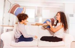 Lycklig pojke- och flickastridighet med hemmastadda kuddar arkivfoton