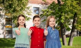 Lycklig pojke och flickor som visar upp tummar Arkivbild