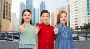 Lycklig pojke och flickor som visar upp tummar Royaltyfria Bilder