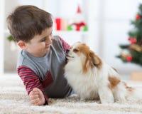 Lycklig pojke och hund för liten unge på jul arkivfoto