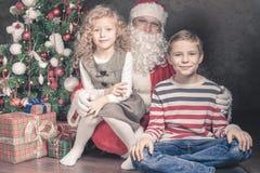 Lycklig pojke och Santa Claus med den stora gåvaasken Royaltyfria Foton