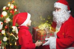 Lycklig pojke och Santa Claus med den stora gåvaasken Arkivfoto