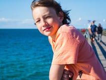 Lycklig pojke på en pir på det baltiska havet arkivbilder