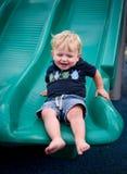 Lycklig pojke på glidbana Royaltyfri Foto