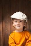 Lycklig pojke på wood plankabakgrund arkivbilder