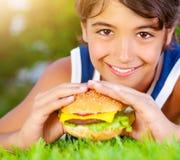 Lycklig pojke som äter hamburgaren Fotografering för Bildbyråer