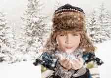 Lycklig pojke som blåser snöflingor i vinterlandskap royaltyfri fotografi