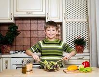 Lycklig pojke som blandar en grönsaksallad i köket. Arkivfoton