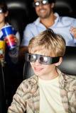 Lycklig pojke som håller ögonen på filmen 3D på teatern Royaltyfria Bilder