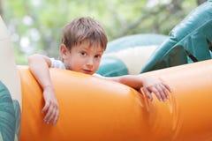 Lycklig pojke som har gyckel på trampolinen utomhus Royaltyfri Fotografi