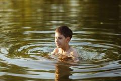 Lycklig pojke som har rolig simning i vattnet Royaltyfri Fotografi