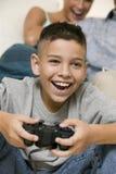 Lycklig pojke som hemma spelar videospel Royaltyfri Bild