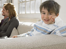 Lycklig pojke som kopplar av på Sofa With Parents At Home Royaltyfri Foto