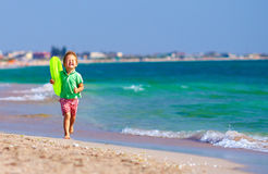 Lycklig pojke som kör stranden som uttrycker fröjd Royaltyfri Bild