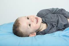 Lycklig pojke som lägger på säng royaltyfria bilder
