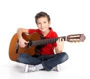 Lycklig pojke som leker på den akustiska gitarren Fotografering för Bildbyråer