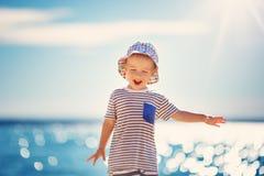 Lycklig pojke som ler på stranden i hatt Arkivbilder