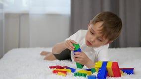 Lycklig pojke som ligger på sängen och spelar med de kulöra kvarteren av konstruktörn som bygger ut ur den lager videofilmer