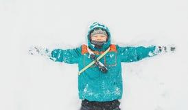Lycklig pojke som ligger på snö fotografering för bildbyråer