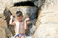 Lycklig pojke som plaskar i vattenfall Royaltyfri Foto