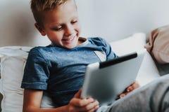 Lycklig pojke som sitter med den digitala minnestavlan i hand royaltyfria foton
