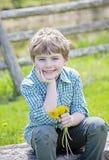 Lycklig pojke som sitter på bänk med buketten av nya valda blommor royaltyfria bilder