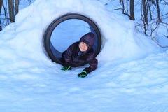 Lycklig pojke som spelar i en snötunnel arkivbilder