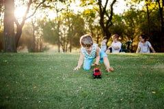 Lycklig pojke som spelar med boll- och leksakbilen på grönt gräs Arkivfoto