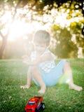 Lycklig pojke som spelar med boll- och leksakbilen på grönt gräs Royaltyfria Bilder