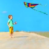 Lycklig pojke som spelar med draken på sommarfält Royaltyfri Fotografi
