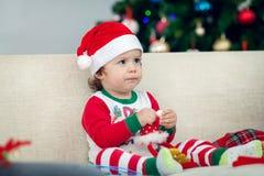 Lycklig pojke som spelar med en julgran i bakgrunden Royaltyfri Fotografi