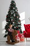 Lycklig pojke som spelar nära julgranen Royaltyfri Foto