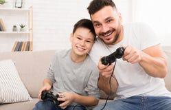 Lycklig pojke som tycker om videospelet med hans pappa som spelar med styrspakar royaltyfri bild