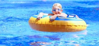 Lycklig pojke som tycker om watersliden arkivfoton