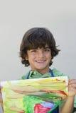 Lycklig pojke som visar hans målning royaltyfri fotografi