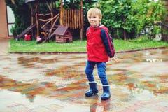 Lycklig pojkebanhoppning i pölar efter regn Royaltyfri Foto