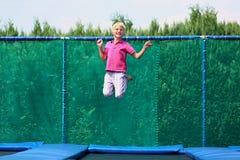 Lycklig pojkebanhoppning på trampolinen Royaltyfri Fotografi