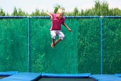 Lycklig pojkebanhoppning på trampolinen Royaltyfri Bild